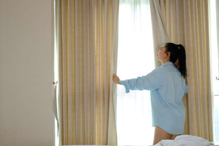 Young woman not wearing pants pulling opening curtains in the bedroom after waking up in the morning