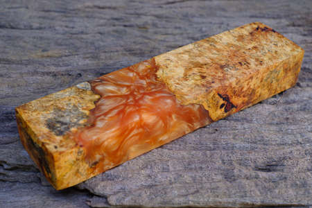 Stick of cut casting epoxy resin burl wood on old wooden table background