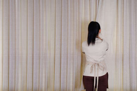 Housemaid closing the curtains on window In hotel room Banque d'images