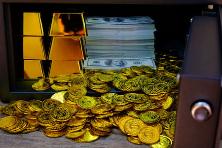 Steel safes box full of coins stack and gold bar and banknote 100 USD on the wooden table