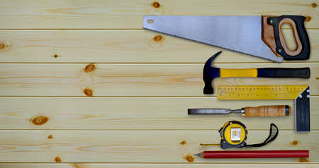 Hammer saw tape measure try square pencil and chisel collection of woodworking handtools on a workbench wooden