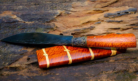 knife custom or Enep in the natural wood scabbard on old table background handmade of Thailand