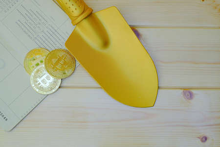 Close up of gold bitcoin coins on bank passbook with a golden shovel on wooden table Archivio Fotografico