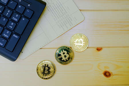 Close up of gold Bitcoin coins on bank passbook with laptop keyboard on wooden table