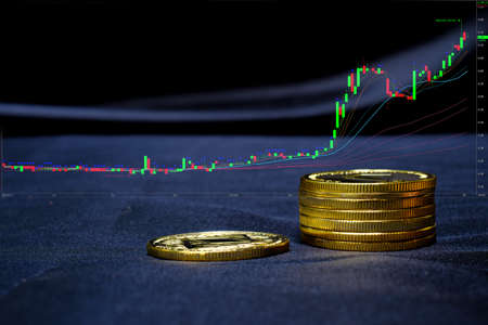 Gold coin cryptocurrency at computer trading chart background