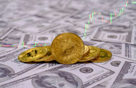 Gold bitcoin coins cryptocurrency on the group of money 100 USD dollars a lot of