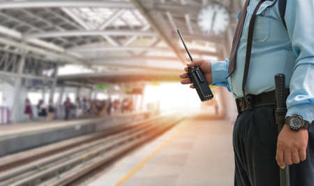 Professional security guard hand holding cb walkie-talkie radio in electric train station, copy space for text. Stock fotó