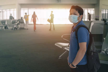 Young asian man in t shirt, protective disposable medical mask in airport.