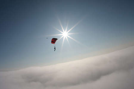 skydiver flying in the background of blue sky and sun Standard-Bild