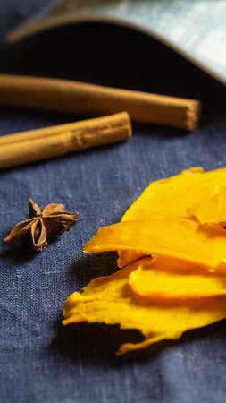 Orange dried mango fruit lie on blue background with a cinnamon