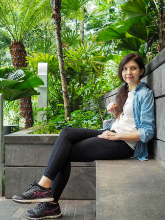 A woman sits at Changi Singapore Airport in the forest Stock Photo