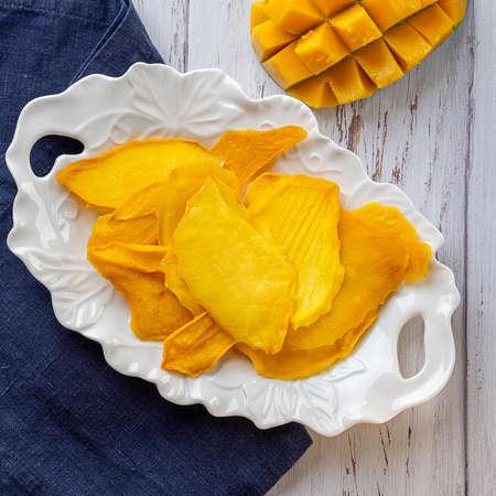 Dried Mango lay on the white plate near the fresh mango