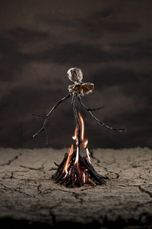Scarecrow in the desert burning on bonfire Stock Photo