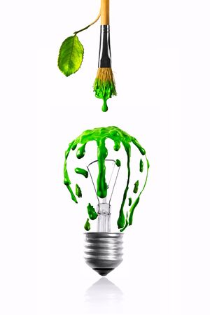 Leaf growing paintbrush dripping green color on eco light bulb photo