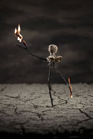 Scarecrow in the desert looking a fire burning from his arms - branches Stock Photo - 17485814