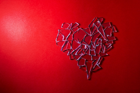 Broken glass love heart on red background