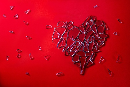 clean heart: Glass love heart on red background Stock Photo