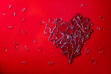 broken love: Glass love heart on red background Stock Photo