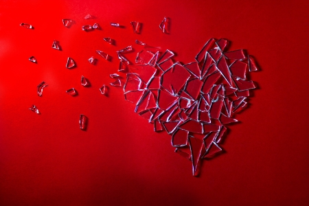 Scattered glass love heart on red background photo