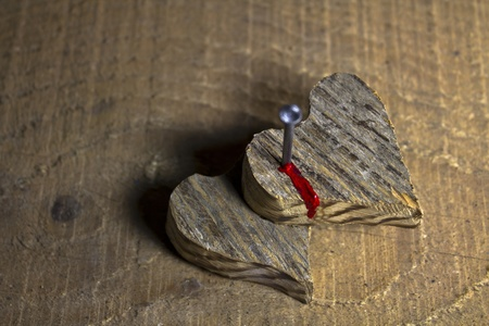 Two wooden heart nailed and bleeding on wooden background Stock Photo - 17485838