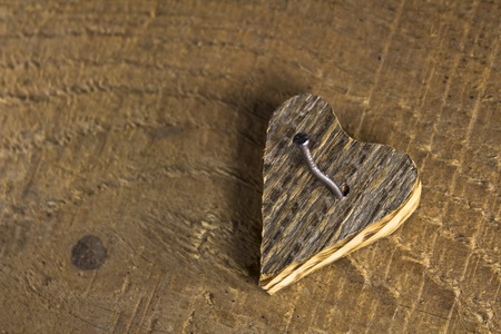 Wooden love heart nailed on wooden background Stock Photo - 17485839