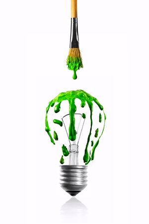 Green color dripping from paintbrush to light bulb photo