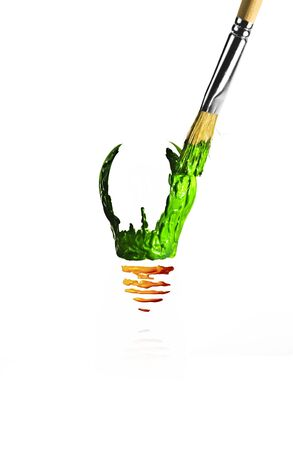 Paintbrush paint a light bulb in green and orange color photo