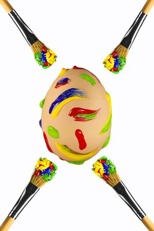 Multicolored strokes painted easter egg with brushes around
