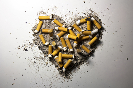 Love heart made of smoked cigarettes and ash Stock Photo