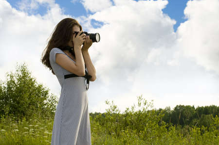Young girl taking photo of summer landscape photo