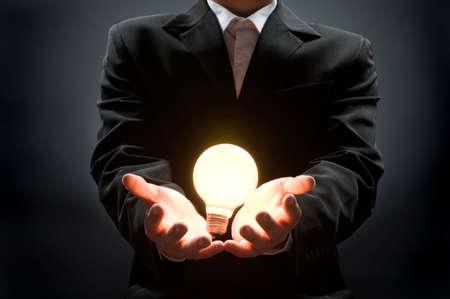 a man pointing to the illuminated bulb photo