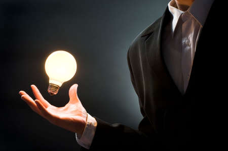 a man pointing to the illuminated bulb photo