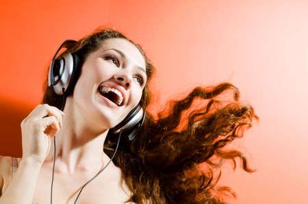auriculares dj: ni�a en los auriculares en el fondo naranja