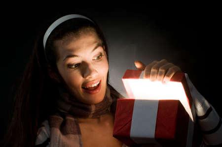 a beautifull girl opening  x-mass magic present photo