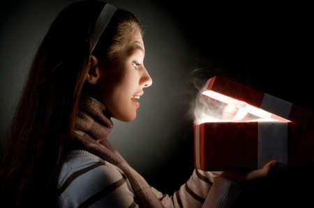a beautifull girl opening  x-mass magic present