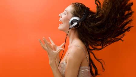 radio activity: girl in headphones on the orange background