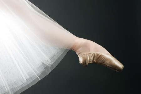 ballet cl�sico: piernas en los zapatos de ballet en un negro backgrounde Foto de archivo
