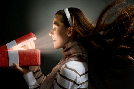 a beautifull girl opening  x-mass magic present