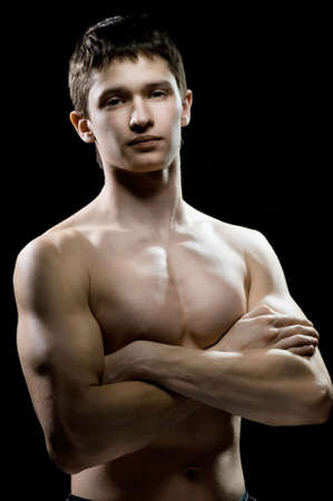 torso only: Muscular male torso on the black background