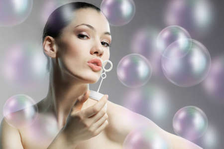 a beauty young woman blowing soap bubbles photo