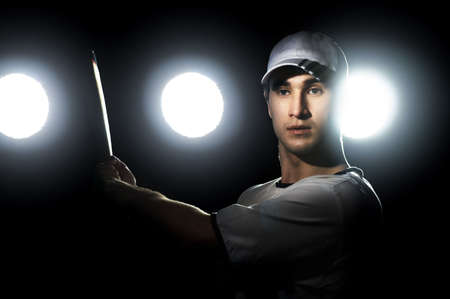 outdoor lighting: Baseball player with a bat in stadium