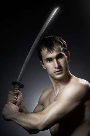 man training with blade on black background photo
