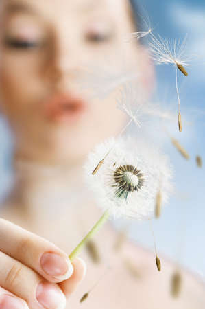 freedom leisure activity: beautiful smiling girl with dandelion in hand