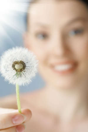 beautiful smiling girl with dandelion in hand photo
