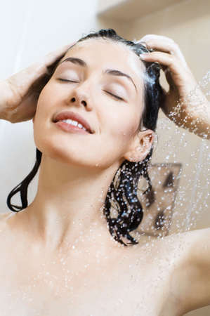 woman washing hair: a beautiful girl standing at the shower