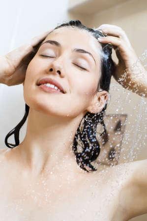 champu: una bella joven de pie en la ducha