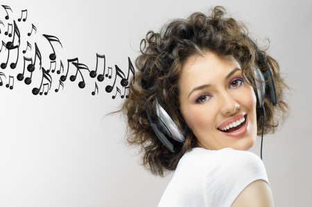 woman listening to music: girl with headphones on the grey background Stock Photo