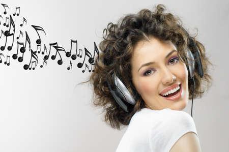 escuchando musica: niña con auriculares en el fondo gris Foto de archivo