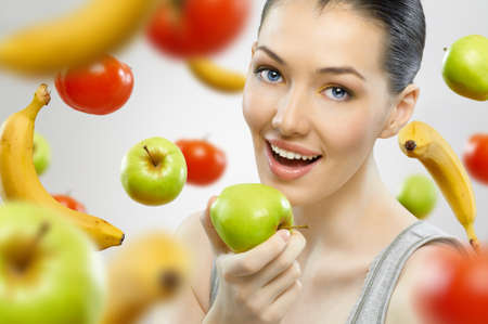 A beautiful slender girl eating healthy fruit photo