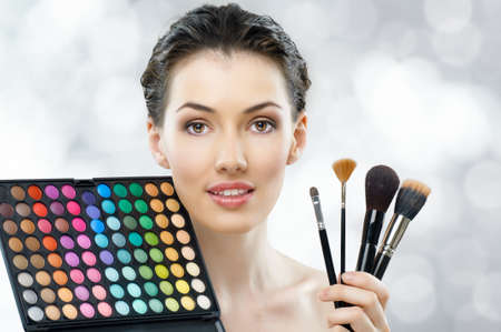 makeup brushes: portrait of a beautiful healthy girl with makeup brushes and color palette